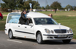 © Licensed to London News Pictures. 21/08/2018. Epsom, UK. Family members sit in the windows of a hearse carrying the coffin of traveller Mikey Connors as it races along a road on Epsom Downs before his burial at a nearby cemetery. 32 year-old Mikey Connors, the nephew of My Big Fat Gypsy Wedding star Paddy Doherty, was killed when his horse-and-cart was hit by a car in Thamesmead on July 28. Photo credit: Peter Macdiarmid/LNP