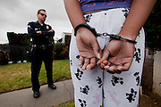 Sergeant Steve Muirhead questions a female auto theft suspect in South Central Los Angeles, Calif. on Jan. 30, 2011. The young lady was detained after a complaint against her from the night before. (photo by Gabriel Romero ©2011)