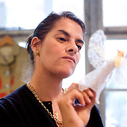 UK. London. Brit Artist Tracy Emin makes a Christmas angle at her studio in East London. It was made from a clothes peg and scraps of lace, felt and thread.