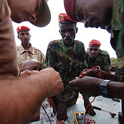"ARTA, Djibouti -- March 25, 2006 -- U.S. Navy Construction Mechanic 1st Class David Borkowski, left foreground, works with Djiboutian Army Sgt. Farah Hassan Boueh to test the resistance in an ignition relay wire.  Borkowski, Leading Petty Officer of the Naval Mobile Construction Battalion 7's Engine Repair Department at Camp Lemonier, is teaching a two-week class on auto maintenance skills to the Djiboutian military at their camp in Arta. .Borkowski said, ""We're having to pull out every part, trouble check it and put it back in. This process assures us that the problems we're seeing are not the result of bad parts. It also has the added effect of teaching these guys how the whole engine goes together."""