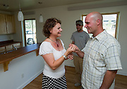 PRICE CHAMBERS / NEWS&amp;GUIDE<br /> Jim and Lisa smile as they receive the key to their new home from David Yogg.