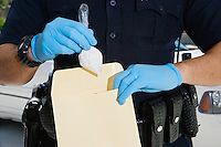 Police Officer Putting Cocaine in Evidence Envelope
