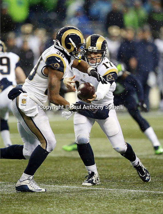 St. Louis Rams quarterback Case Keenum (17) hands off the ball to St. Louis Rams running back Todd Gurley (30) during the 2015 NFL week 16 regular season football game against the Seattle Seahawks on Sunday, Dec. 27, 2015 in Seattle. The Rams won the game 23-17. (©Paul Anthony Spinelli)