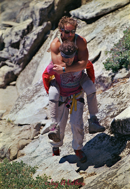 Mike Corbett carries his climbing partner, Mark Wellman, away from the edge of  El Capitan after they completed an eight-day climb of the Shield route.  July 1989.