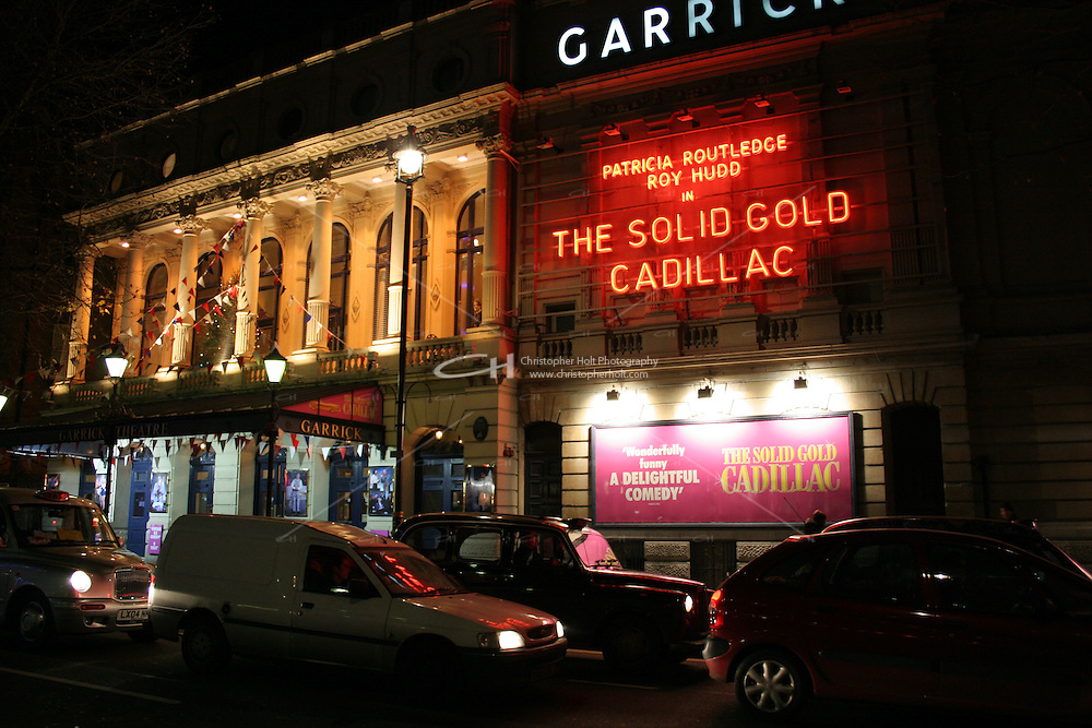 traffic passing garrick theatre at night in london