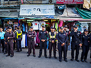 01 AUGUST 2018 - BANGKOK, THAILAND:     Bangkok code enforcement officers wait to start the process of closing night market stands on Khao San Road in Bangkok. Khao San Road is Bangkok's original backpacker district and is still a popular hub for travelers, with an active night market and many street food stalls. The Bangkok municipal government went through with it plans to reduce the impact of the street market on August 1 because city officials say the venders, who set up on sidewalks and public streets, pose a threat to public safety and could impede emergency vehicles. Venders are restricted to working from 6PM to midnight and fewer venders will be allowed to set up on the street. It's the latest in a series of night markets and street markets the city has closed.     PHOTO BY JACK KURTZ
