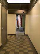 a very large American flag hanging in the lobby of an office