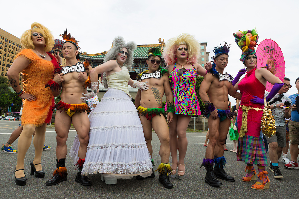 "Drag queens and male dancers pose in front of some for a photo. The annual march through Taipei's city streets is the largest in Asia, with well over 50 000 people taking part. The 2014 event had the theme ""Walk in Queer's Shoes"", to encourage the wider community to lend their support for equal marriage rights."