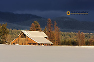 Days last light on snowy barn in Whitefish, Montana, USA