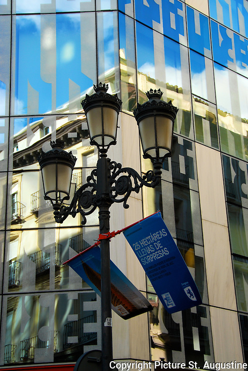 Three light lamp post in front of glass building with another building reflected in the architecture.