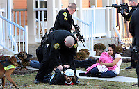Chris Bergin / The Star Press..Suspects are placed in handcuffs following a shooting at 906 S. Jefferson Street at Millenium Place Wednesday evening. One person was shot twice and taken to Ball Memorial Hospital. Police are still searching for a white car that they say was involved in the shooting.