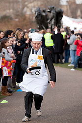 © Licensed to London News Pictures. 21/02/2012. LONDON, UK. Labour MP Ian Murray tosses a pancake as he takes part in a pancake race outside the Houses of Parliament today (21/02/12). Lords, Members of Parliament and political journalists today took part in the 2012 'Rehab Parliamentary Pancake Race' in aid of disability charity Rehab. The parliamentary team took the trophy after an extra lap was run due to widespread cheating. Photo credit: Matt Cetti-Roberts/LNP