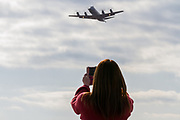 A female Japanese aircraft enthusiast photographs  a Lockheed EP3 Orion ELINT signals reconnaissance aircraft as it takes  off from Naval Air Facility, Atsugi near Yamato, Kanagawa, Japan. Wednesday January 23rd 2019