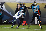 Jacksonville Jaguars free safety Tashaun Gipson (39) looks on and Seattle Seahawks wide receiver Doug Baldwin (89) makes the tackle as Jacksonville Jaguars cornerback A.J. Bouye (21) leaps and intercepts a third quarter pass that gives the Jaguars the ball at their own 2 yard line during the 2017 NFL week 14 regular season football game against the Seattle Seahawks, Sunday, Dec. 10, 2017 in Jacksonville, Fla. The Jaguars won the game 30-24. (©Paul Anthony Spinelli)