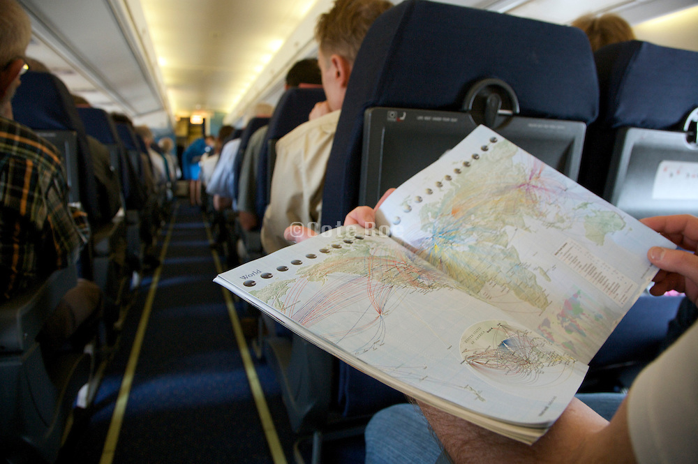 passenger reading in-flight magazine with all the destinations page