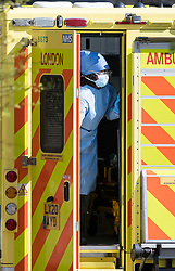 © Licensed to London News Pictures. 23/04/2020. London, UK. A medic in PPE is seen entering an ambulance in Primrose Hill, north London during a pandemic outbreak of the Coronavirus COVID-19 disease. The public have been told they can only leave their homes when absolutely essential, in an attempt to fight the spread of coronavirus COVID-19 disease. Photo credit: Ben Cawthra/LNP. Photo credit: Ben Cawthra/LNP