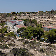 The centre where the migrants and refugees have to spend a few days or weeks before being transferred to the Italian mainland is hidden behind a hill, not visible to the thousands of tourists on the island