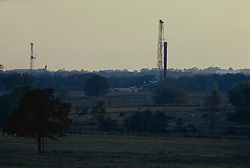 Stock photo of an on-shore rig in the distance through the fields