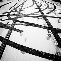 Tyre tracks and foot prints in light snow in an urban environment