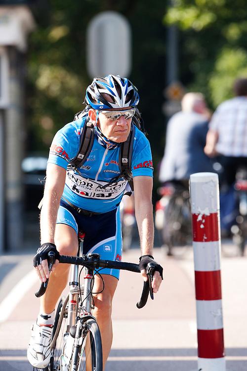 Een forensende wielrenner rijdt in de buurt van het Ledig Erf in Utrecht.<br /> <br /> A commuting cyclist is passing Ledig Erf in Utrecht.