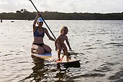 2 year old girl & her mother playing on a Stand Up Paddle Board in Currimundi Lake, Sunshine Coast, Queensland, Australia