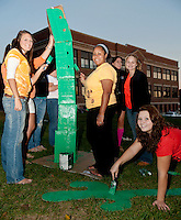Senior classmates Bree Martin, Jazmine Jackson and Angelica Platon paint cactus for their desert themed float to march in the Laconia High School Homecoming parade tomorrow evening.  (Karen Bobotas/for the Laconia Daily Sun)