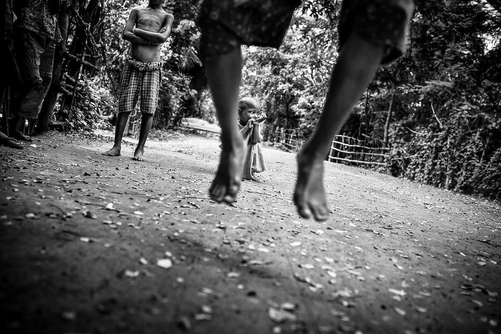 Children jump rope in a rural hamlet outside Yangon, Myanmar