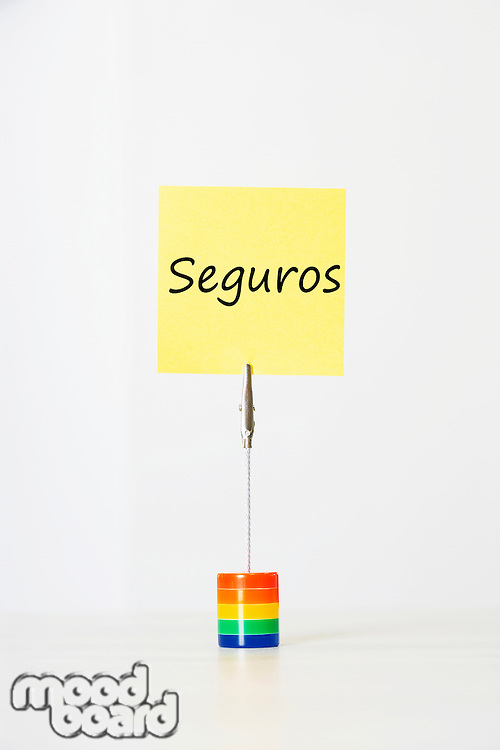 Sticky notepaper with Spanish text Insurance clipped to a multicolored card holder