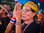 "15 NOVEMBER 2013 - BANGKOK, THAILAND: A Thai woman prays for Bhumibol Adulyadej, the King of Thailand, during an anti-government protest in Bangkok. Thai royalists accuse the government of Prime Minister Yingluck Shinawatra of not being supportive enough of the monarchy. Tens of thousands of Thais packed the area around Democracy Monument in the old part of Bangkok Friday night to protest against efforts by the ruling Pheu Thai party to pass an amnesty bill that could lead to the return of former Prime Minister Thaksin Shinawatra. Protest leader and former Deputy Prime Minister Suthep Thaugsuban announced an all-out drive to eradicate the ""Thaksin regime."" The protest Friday was the biggest since the amnesty bill issue percolated back into the public consciousness. The anti-government protesters have vowed to continue their protests even though the Thai Senate voted down the bill, thus killing it for at least six months.     PHOTO BY JACK KURTZ"