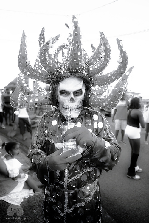 Young man wearing a devil carnival costume and drinking water in Le Lorrain, Martinique. 19 February 2006.