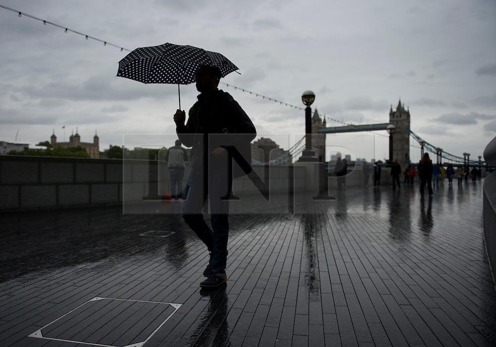 © Licensed to London News Pictures. 29/05/2015. London, UK. Members of the public shelter underneath umbrellas near Tower Bridge in central London on a wet and rainy morning.. Photo credit: Ben Cawthra/LNP