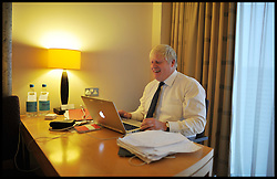 Boris Johnson laughing as he writes his speech in his room at The Conservative Party Conference at ICC, Birmingham, on the second day of the Party Conference, Monday October 8, 2012. Photograph by Andrew Parsons / i-Images