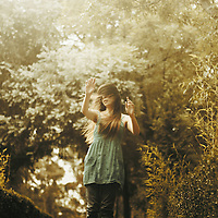 outdoors portrait of a young girl hiding her face with arms outstretched