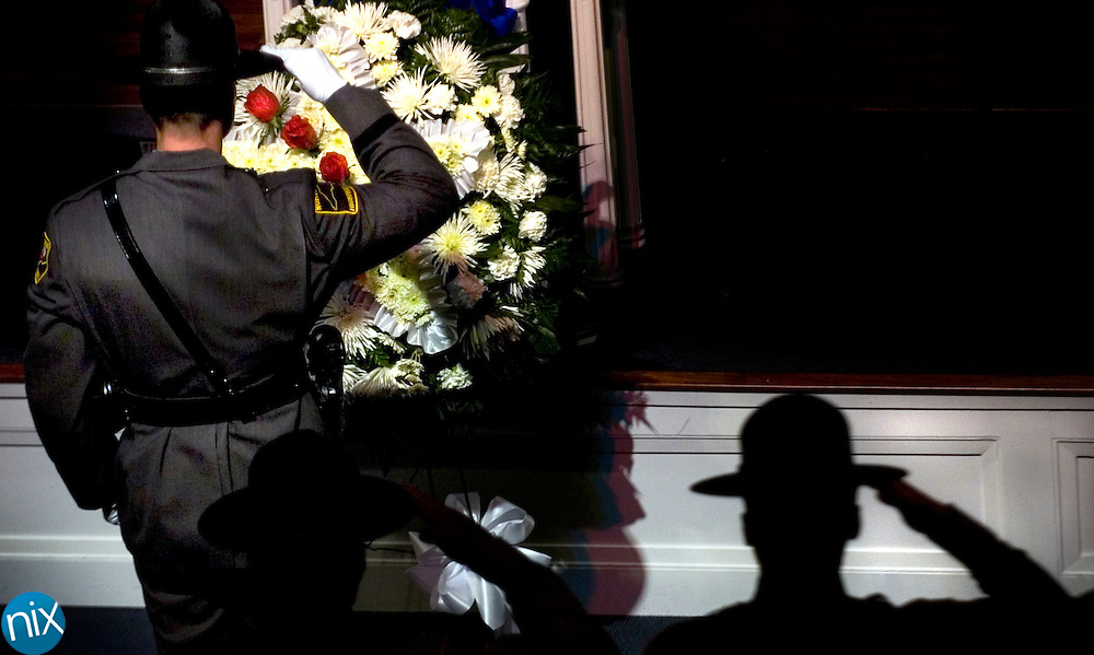 Members of the North Carolina Highway Patrol salute a memorial wreath after an officer placed a rose on the wreath in honor of Andrew Stocks, who was killed in the line of duty last year, during the North Carolina Peace Officers Memorial service at Charity Baptist Church in Kannapolis Wednesday. Law enforcement from accross the state were at the church to honor the five officers who lost their lives over the past year.