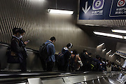 Commuters use mobile phones and smart phones on an escalator in Nagatacho Station in Tokyo, Japan. Monday May 2nd  2016