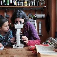 Nederland, Amsterdam , 31 maart 2015.<br /> Elisabeth Erasmus geeft haar kinderen thuis onderwijs.<br /> op de foto moeder elisabeth geeft dochter Maya microscooples les terwijl dochter Malaika een boek leest.<br /> Foto:Jean-Pierre Jans