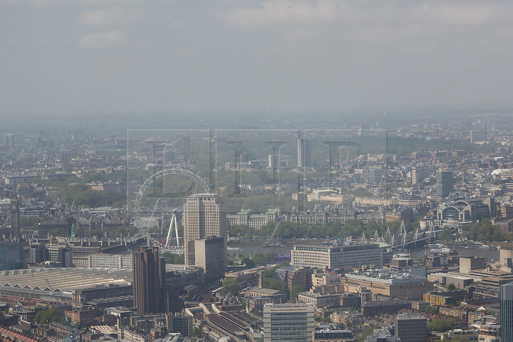 © Licensed to London News Pictures. 13/06/2016. LONDON, UK.  An aerial view of London showing the London Eye during sunny spring weather today. Haze and pollution is seen hanging towards the horizon.  Photo credit: Vickie Flores/LNP