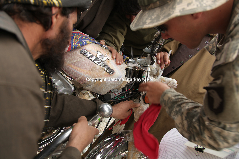 US troops form the 101st Airborne Division, 2-502 Infantry Battalion, use stickers to try and register Afghan motorcycles in Zhari district, in Kandahar province, southern Afghanistan.  The decals are assigned to individual riders and matched with their biometric data, including finger prints and iris scans. It is part of a military plan to try and limit the Taleban's freedom of movement around the hamlest where their organisation was born.
