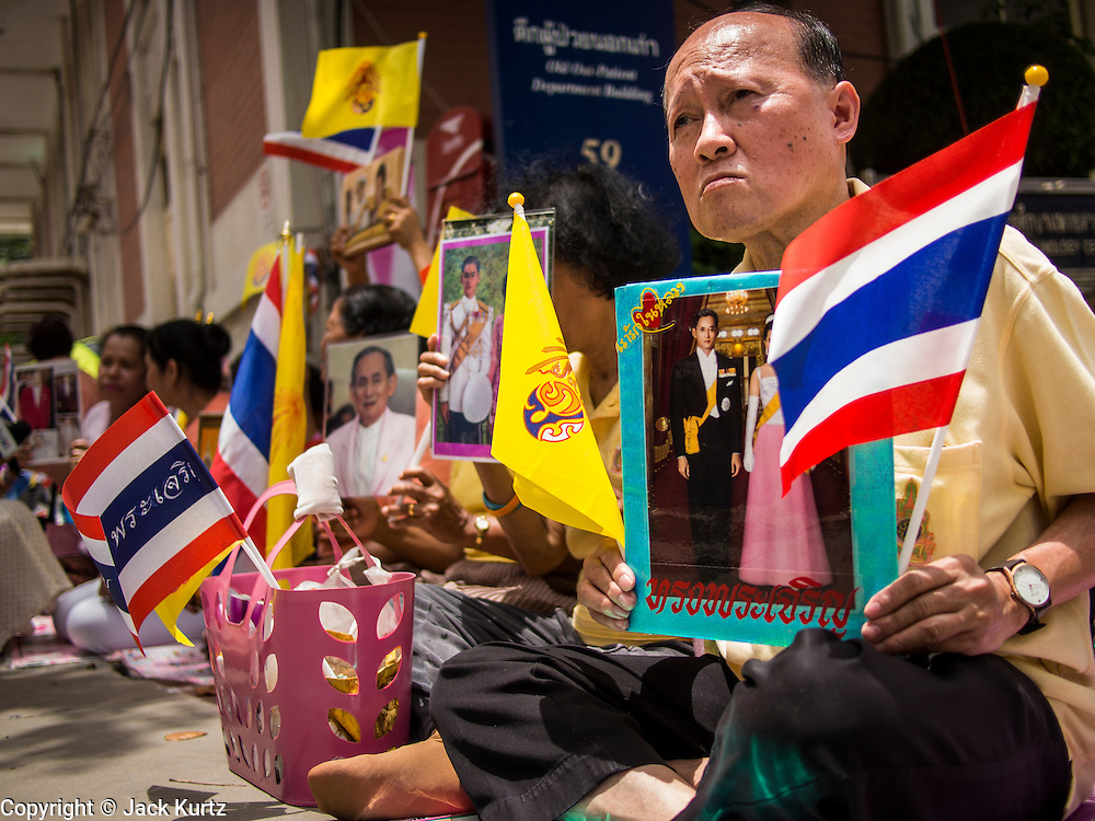 01 AUGUST 2013 - BANGKOK, THAILAND:       People wait in front of Siriraj Hospital with pictures of Bhumibol Adulyadej, the King of Thailand, before the King left the hospital Thursday. The King, 85, was discharged from Bangkok's Siriraj Hospital, where he has lived since September 2009. He traveled to his residence in the seaside town of Hua Hin, about two hours drive south of Bangkok, with his wife, 80-year-old Queen Sirikit, who has also been treated in the hospital for a year.   PHOTO BY JACK KURTZ