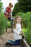 Girl (5-6) gardening with mother in countryside