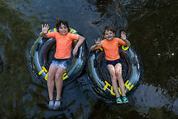 © Licensed to London News Pictures. 07/08/2020. CHORLEYWOOD, UK. Evan (L), aged 9, and Oscar, aged 7, relax on rubber rings in the cool waters of the River Chess near Chorleywood, Hertfordshire.  The forecast is for temperatures to continue to exceed 30C for the next few days. (Parental permission obtained)  Photo credit: Stephen Chung/LNP