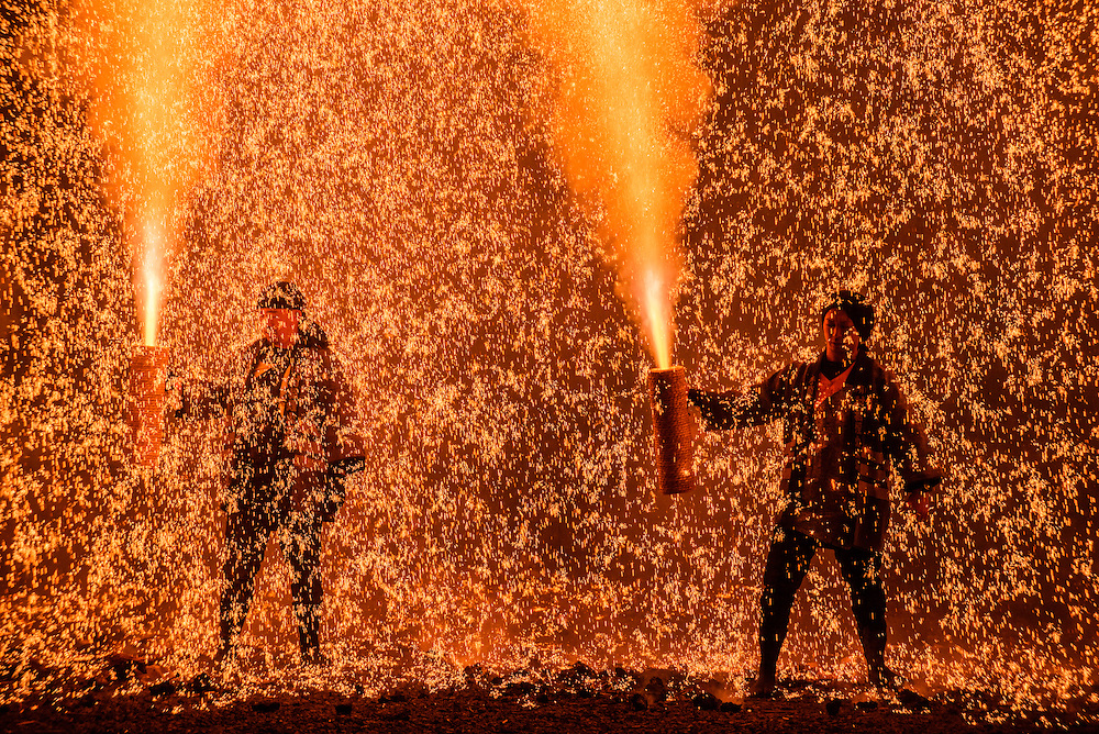Men launch handheld fireworks known as tezutsu hanabi at Inaba Shrine in Gifu, Japan.