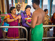 05 JUNE 2015 - KUALA LUMPUR, MALAYSIA:  Midday prayers at Sri Mahamariamman Temple, the oldest functioning and most important Hindu temple in Malaysia. The principal deity in the temple is Mariamman,  a deity that is popularly worshipped by overseas Indians, especially Tamils, because she is looked upon as their protector during the sojourn to foreign lands. Mariamman is a manifestation of the goddess Parvati, an incarnation embodying Mother Earth with all her terrifying force. She is associated with disease and fever and protects her devotees from unholy or demonic events.    PHOTO BY JACK KURTZ