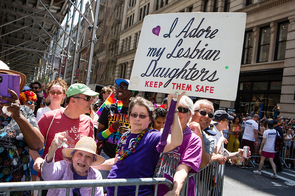 "New York, NY - 30 June 2019. The New York City Heritage of Pride March filled Fifth Avenue for hours with participants from the LGBTQ community and it's supporters. A woman spectator carries a sign reading ""I adore my Lesbian Daughters."""
