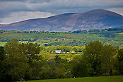 Farmhouse and distant view of Knockmealdown Mountains at Glengoura, County Cork, Ireland