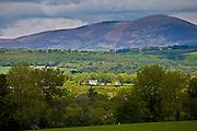 Farmhouse and distant view of Knockmealdown Mountains at Glengoura, County Cork, Ireland