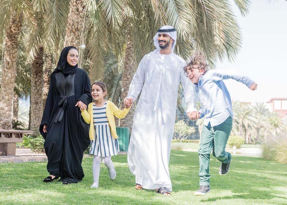 Arab Emirati family of mother, father and two children walking outdoors in green park. They are happy, smiling and the young girl and boy hold the hands of their parents ans they walk along in a line enjoying the leisure time together.