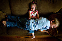 Emma Roberts, 5, plays on the couch in her family's Coeur d'Alene home Tuesday with her brother Justin Roberts, 8. Emma, who has Down syndrome, is being featured in a national Down syndrome awareness video that will be played on one of the giant television screens in Times Square.
