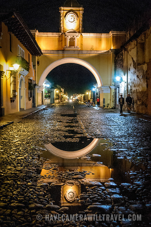 The archway over the street of the convent of Santa Catalina in central Antigua, Guatemala, with the water from recent rain reflecting the lights on the cobblestone street.