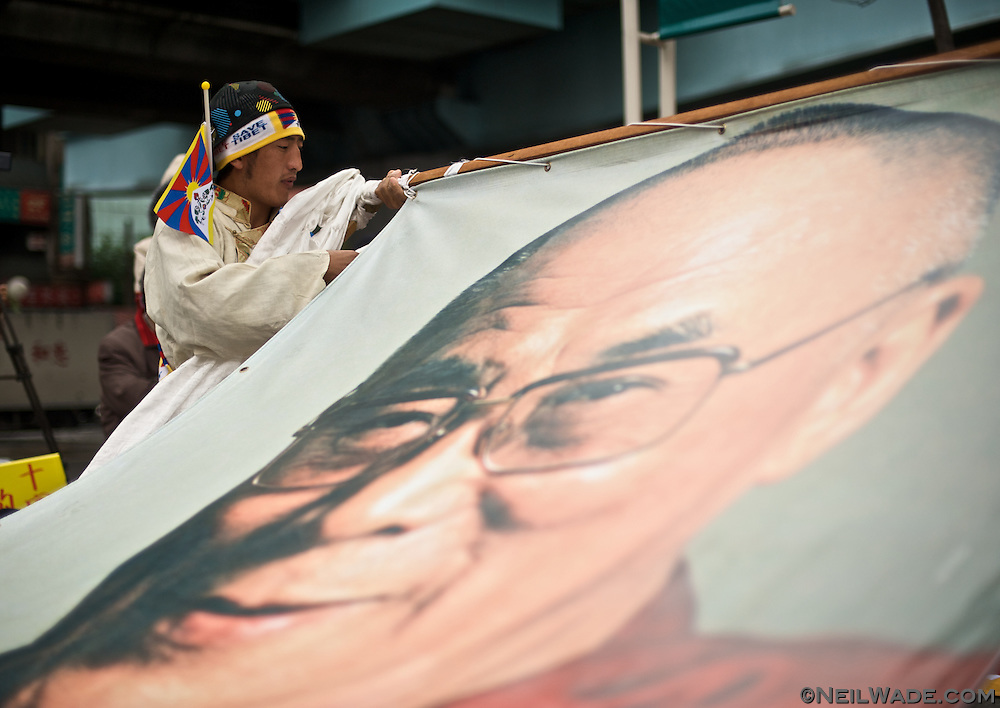 A man dressed in traditional Tibetan clothes prepares a giant picture of the Dali Lama for a march in Taipei, Taiwan.